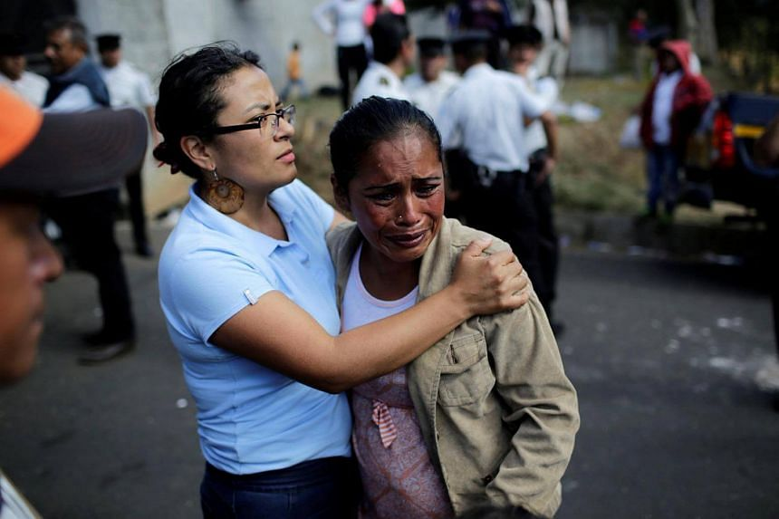 Family members react as they wait for news of their loved ones after a fire broke out at the Virgen de Asuncion home in San Jose Pinula on the outskirts of Guatemala City on March 8, 2017.