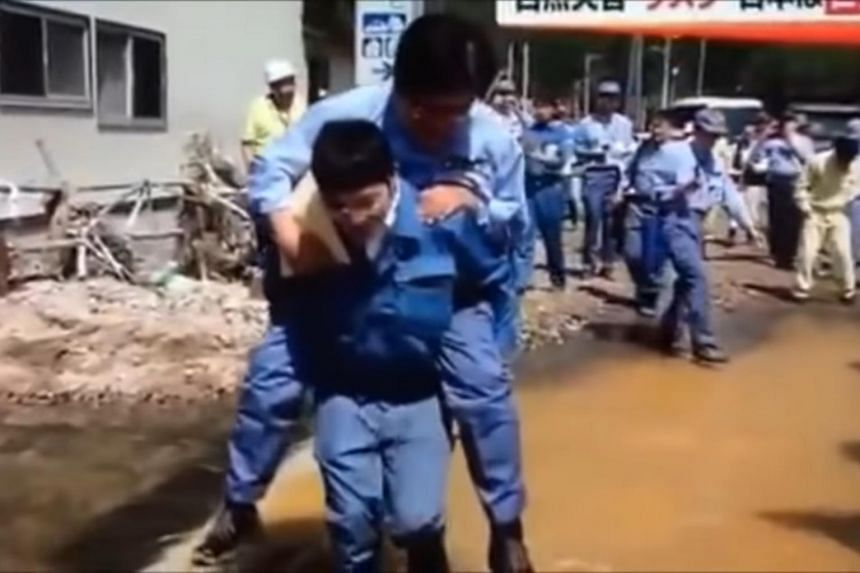 Mr Shunsuke Mutai, parliamentary vice-minister for reconstruction, was seen riding on the back of a younger man over a large puddle of streaming water while visiting the hard-hit northern town of Iwaizumi.