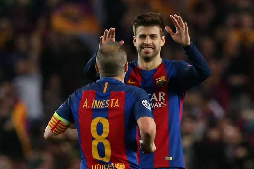 Barcelona's Andres Iniesta celebrating with Gerard Pique after Paris Saint-Germain's Layvin Kurzawa scored an own goal.