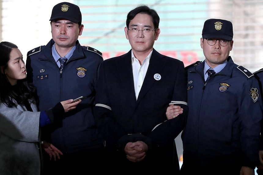 Samsung group leader Lee Jae Yong is escorted by police officers as he arrives at the special prosecutors' office for questioning in Seoul, South Korea, on Feb 25, 2017.