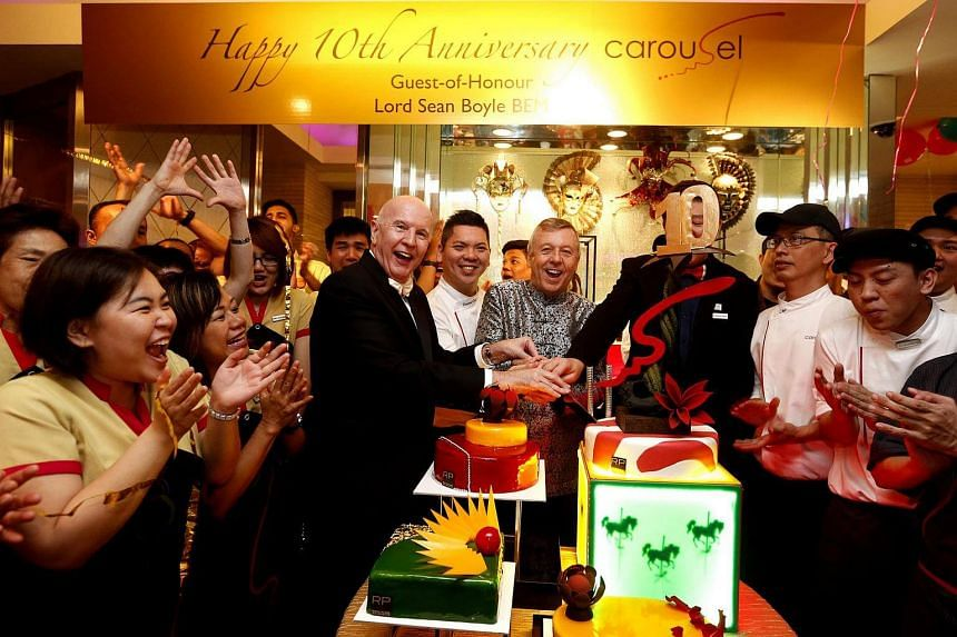 Guest of honour Lord Sean Boyle (centre in black coat) and Mr Patrick Fiat, general manager of Royal Plaza on Scotts, cutting a giant cake with restaurant staff at Carousel.