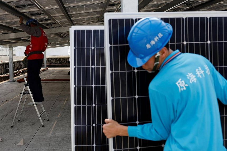 A prisoner (left) places solar panels on the roof of Pingtung Prison in Pingtung, Taiwan.