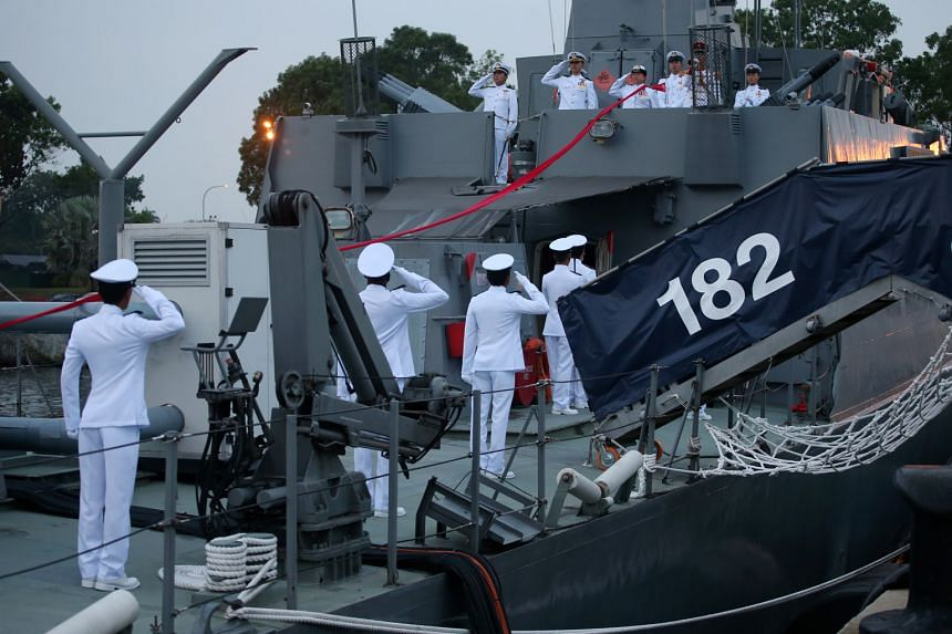 Above: Singapore Navy sailors bade farewell to the patrol vessel during the ceremony, as flags on the warship were lowered for the last time on RSS Independence.