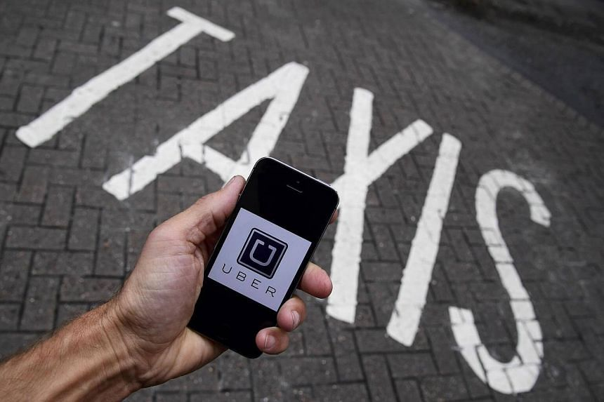 A photo illustration shows the Uber app logo displayed on a mobile telephone.