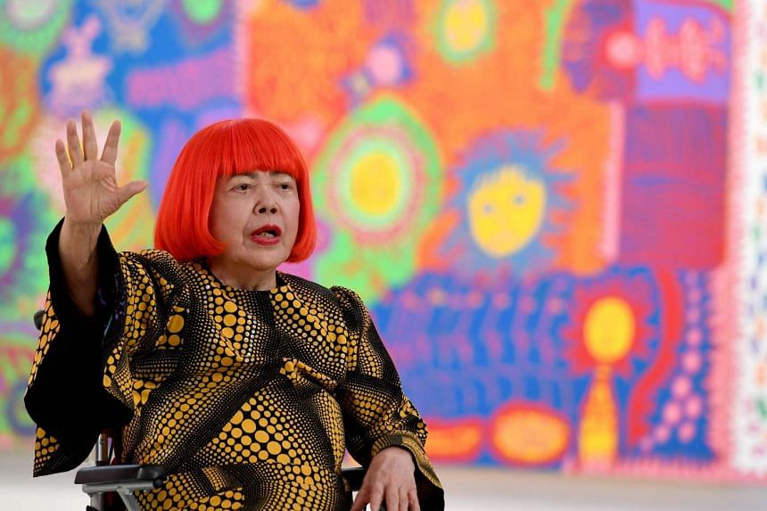 Japanese artist Yayoi Kusama waves at a photo session during a press preview of her exhibition titled My Eternal Soul at the National Art Center in Tokyo on Feb 21, 2017.