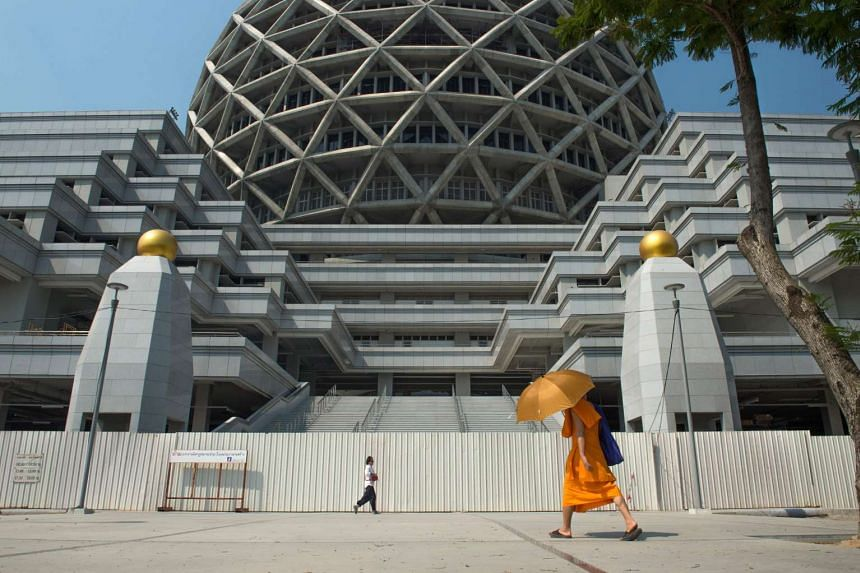 A Buddhist monk walks past a building in the Wat Dhammakaya temple grounds on March 1, 2017.