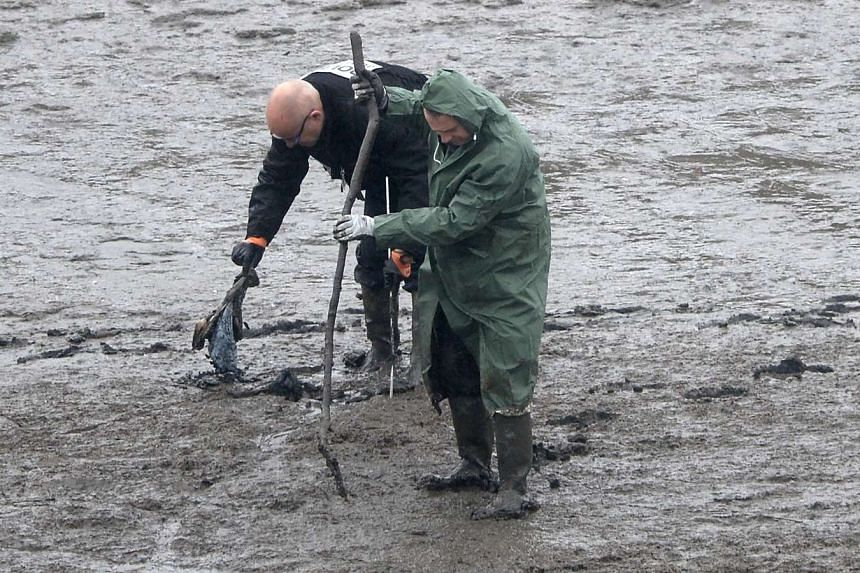 Police officers search the swampy bank of the river Aulne near Caouissin's house, March 9, 2017.