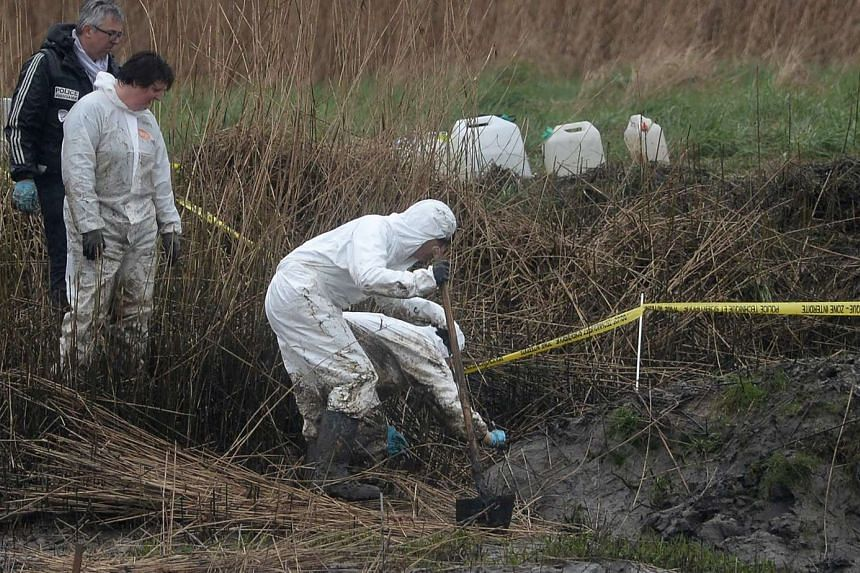 Police officers search on the swampy bank of the river Aulne near the Caouissin's house in Pont-de-Buis-lès-Quimerch, France.