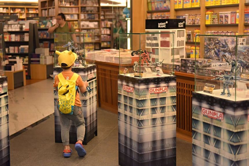 A child looking into Kinokuniya's brand new Gundam showcase, where figurines are put up on display as well as on sale.
