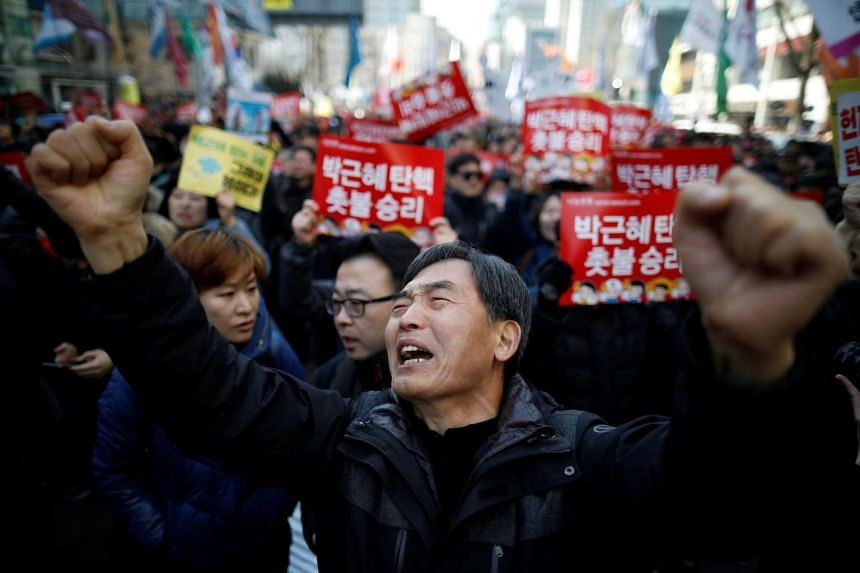 People reacting after hearing that South Korea's Constitutional Court upheld the impeachment of President Park Geun Hye.