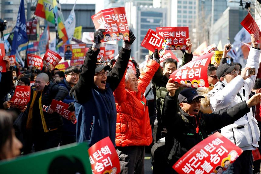 People celebrating after hearing that South Korea's Constitutional Court upheld the impeachment of President Park Geun Hye.