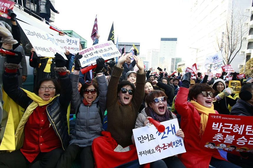 South Koreans cheer after the court's ruling on the impeachment of South Korean President Park Geun Hye near the Constitutional Court in Seoul, South Korea on March 10, 2017.