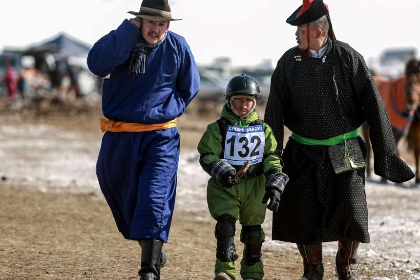 "A Mongolian child jockey preparing to compete in the ""Dunjingarav 2017"" spring horse race on the outskirts of Ulan Bator."