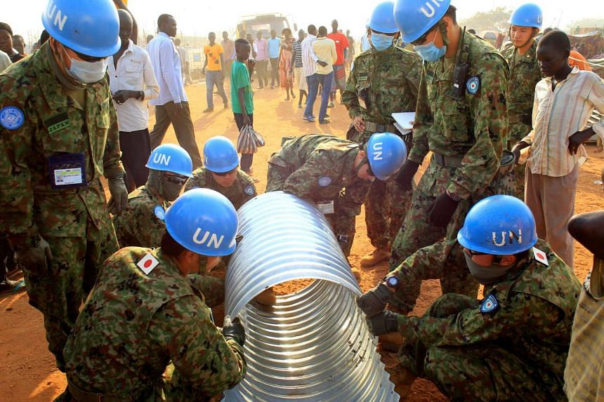 A file photo of United Nations Mission in South Sudan (UNMISS) peacekeepers from Japan assembling a drainage pipe at Tomping camp in Juba, South Sudan, in January 2014.