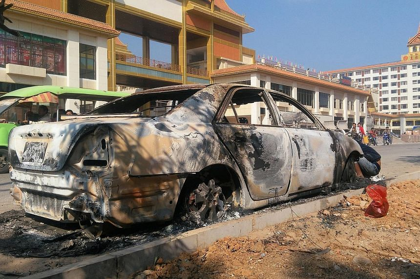 A burnt car in Laukkai, which bore the brunt of clashes between ethnic groups and security forces. About 30 people were killed this week in an attack by ethnic Chinese insurgents as thousands escaped to China.