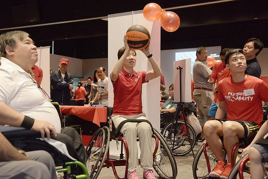 """Minister Grace Fu, with Wheelchair Basketball Association members, giving the sport a shot. With improved access to public facilities, """"everyone can participate more fully in sports and the arts"""", she said."""