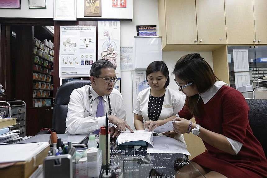 Dr Lee Yik Voon, 54, in discussion with nurse See Chue Win (centre), 33, and care coordinator Landy Lee, 24, yesterday. Dr Lee has been part of the primary care network since late 2015. From next month, GPs will be able to apply to join such a networ