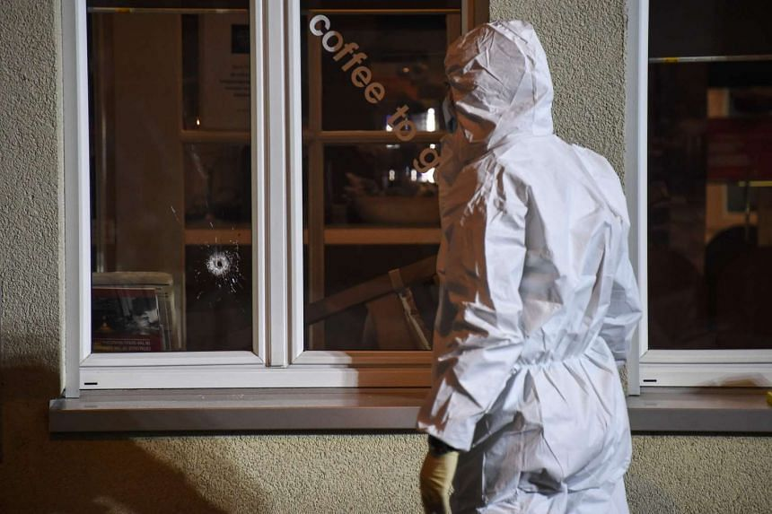 Police collecting evidence at the site of a shooting in the city of Basel, north-west Switzerland. Two men shot dead two people and seriously injured a third. The suspects are on the run.