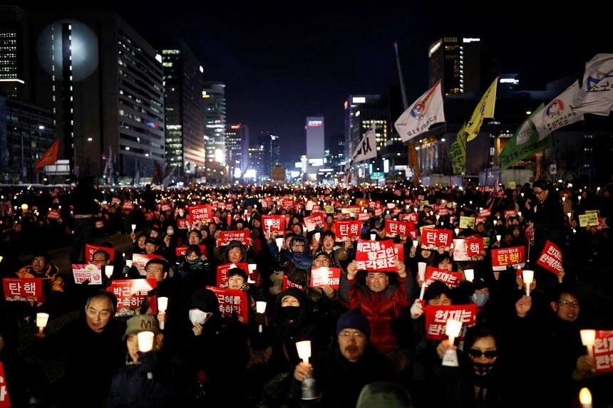 People attending a protest against South Korean President Park Geun Hye.