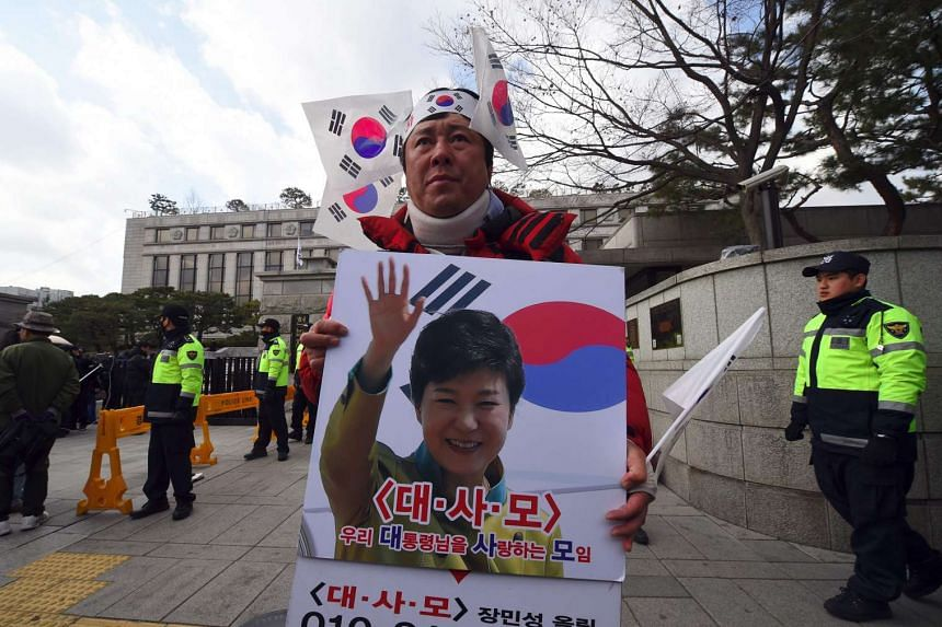 A pro-government activist holding a portrait of South Korea's President Park Geun Hye to oppose the impeachment of the President in front of the Constitutional Court in Seoul, South Korea.