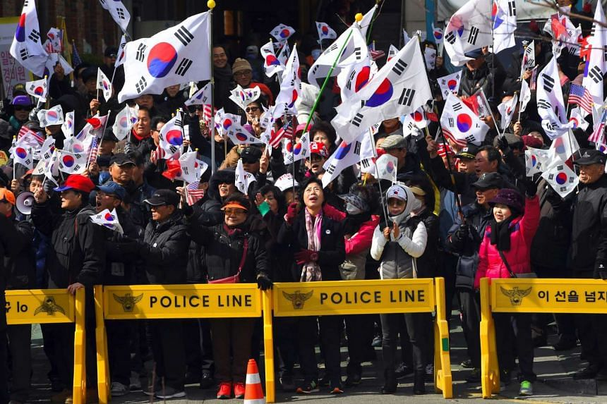 Pro-government activists waving national flags during a rally opposing the impeachment of South Korea's President Park Geun Hye near the Constitutional Court in Seoul, South Korea.