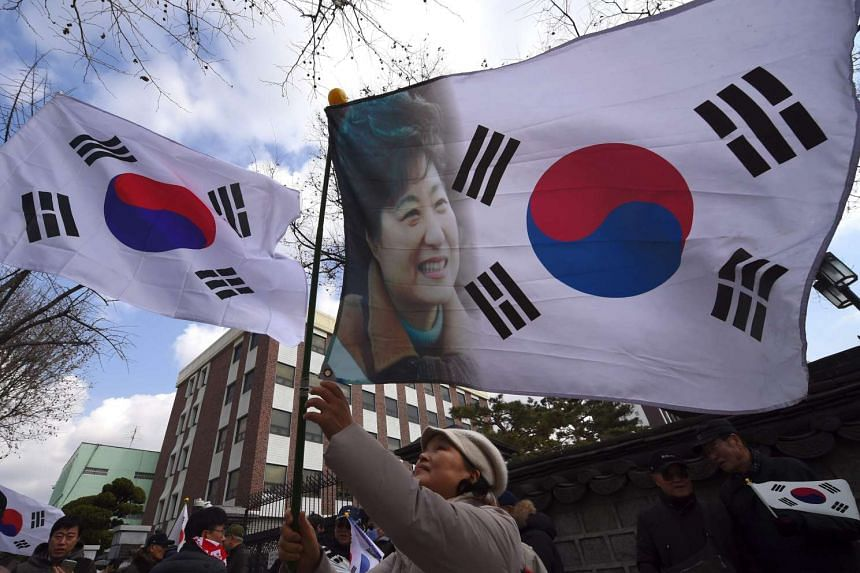 A pro-government activist waving a national flag showing a portrait of South Korea's President Park Geun Hye during a rally opposing the impeachment of the President near the Constitutional Court in Seoul, South Korea.