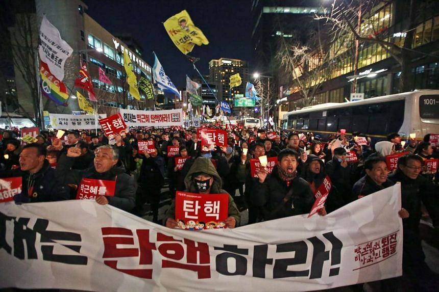South Koreans shouting slogans and holding banners reading 'Park Geun Hye Impeachment' during a rally against South Korean President Park Geun Hye near the Constitutional Court in Seoul, South Korea.