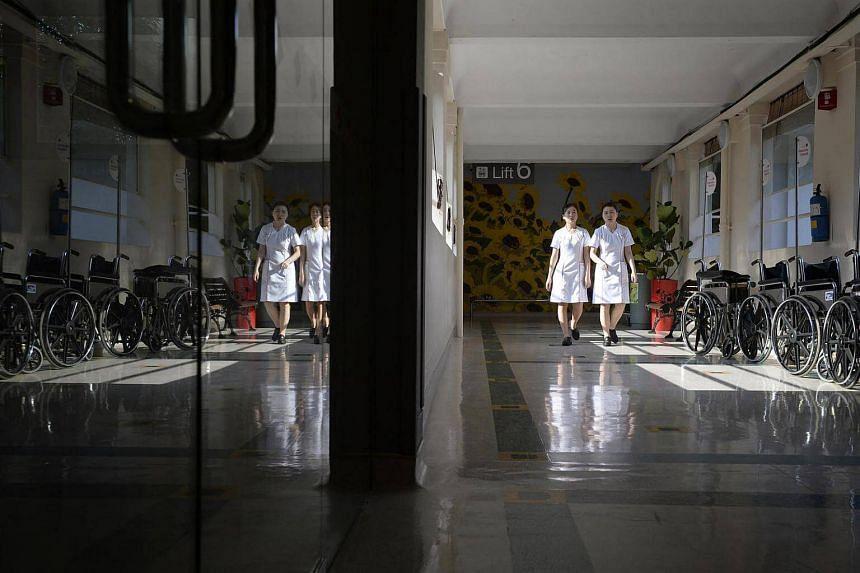 Two staff nurses walk down a corridor outside a ward at Alexandra Hospital on June 29, 2015.