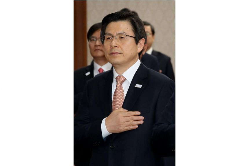 Acting President Hwang Kyo Ahn salutes the national flag during a Cabinet meeting in Seoul on March 7, 2017.