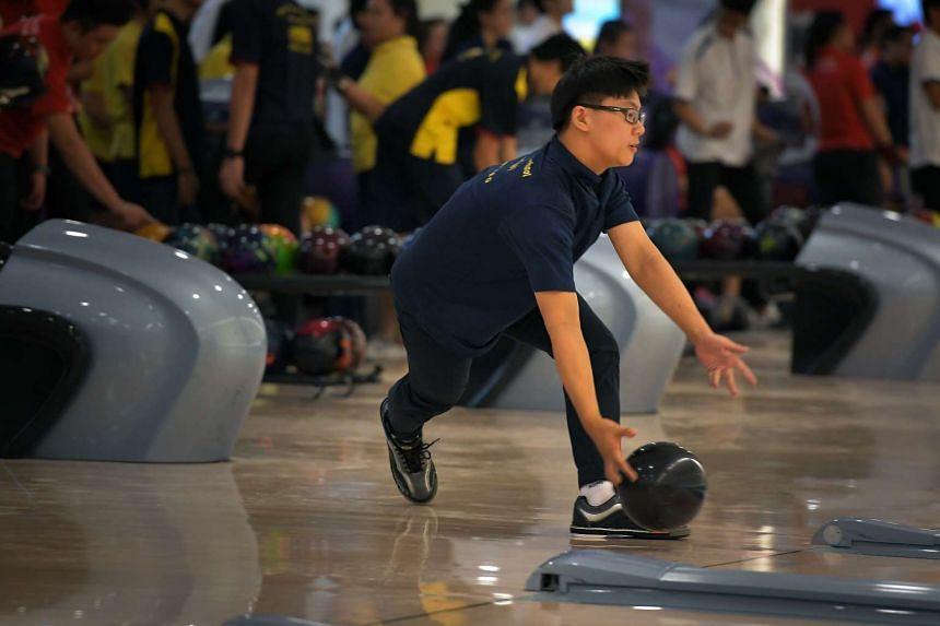 """ACS (Barker)'s Jonathan Vincent Lum, 15, releasing the bowling ball using the """"two-handed"""" style on his way to the singles title. It was the only B Division boys' category that Singapore Sports School missed out on."""