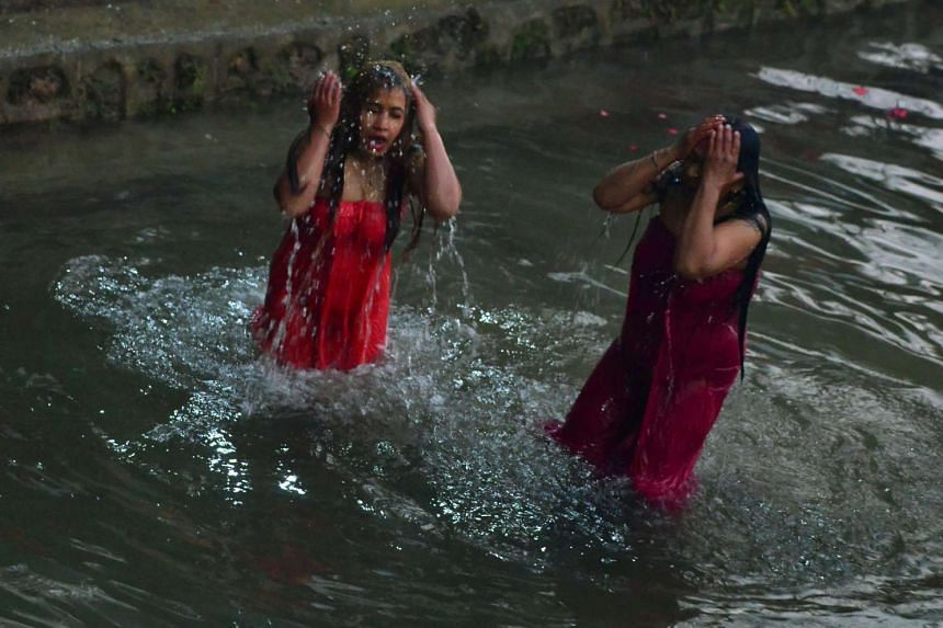 Nepalese Hindu devotees gather to bathe in the Shali River on the outskirts of Kathmandu on Jan 12, 2017.
