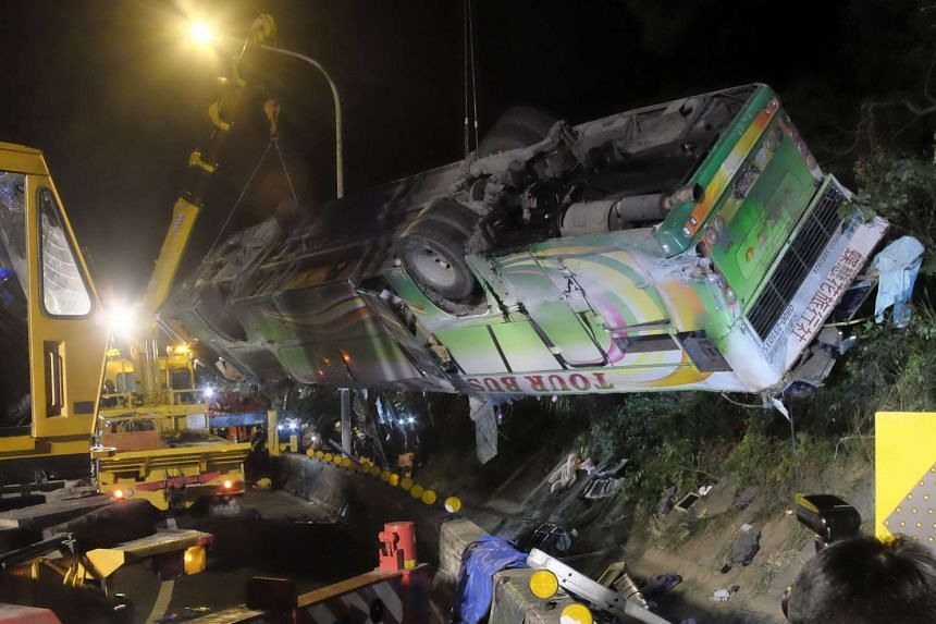 A bus that crashed along a highway is lifted by cranes in Taipei on Feb 14, 2017
