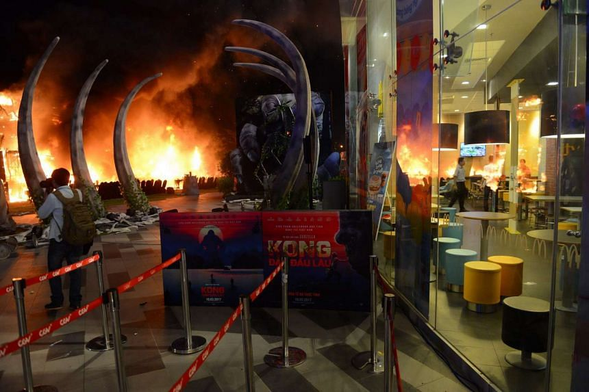 A photographer taking picture of a fire on a giant model of King Kong during the premiere of the Kong: Skull Island in Ho Chi Minh City on March 9, 2017.