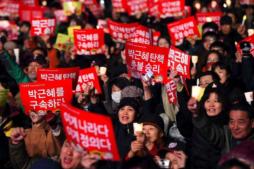 """South Korean demonstrators holding up banners reading """"Park Geun-Hye impeachment, candlelight victory!"""" during a rally demanding the arrest of the impeached president in Seoul on Friday (March 10)."""