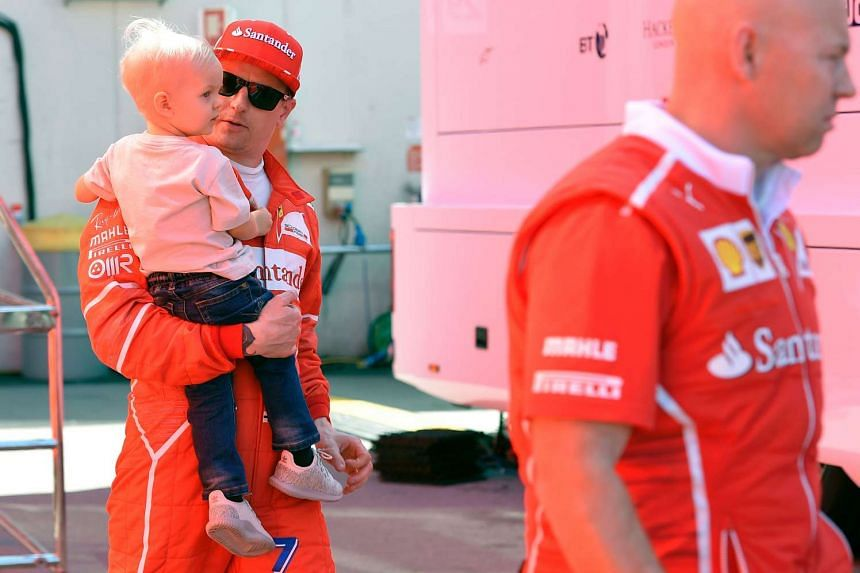 Raikkonen holds his son in his arms on March 10, 2017, during the fourth day of the second week of tests ahead of the Formula One Grand Prix season.