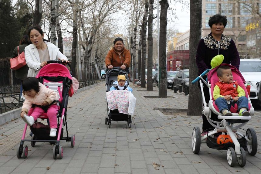 People push baby carriages outside the Ritan Park in Beijing, China on March 11, 2017.