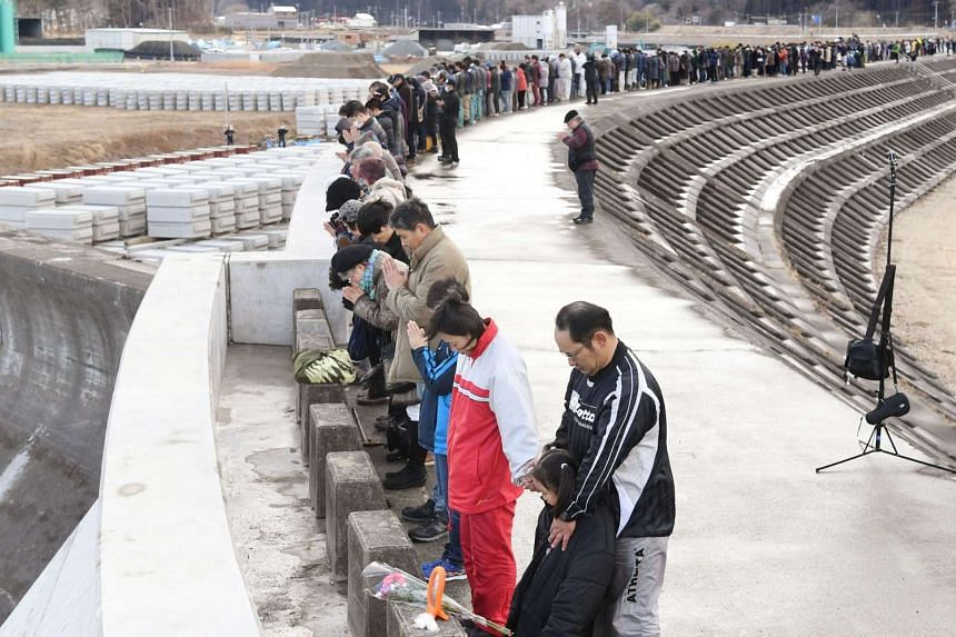 People observe a moment of silence at  the time when the magnitude 9.0 earthquake struck off Japan's coast in 2011, atop of a seawall in Iwate on March 11, 2017.