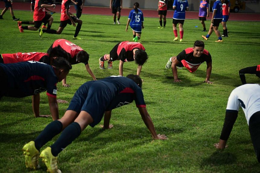 Irfan Fandi warms up with Saturday Night Light (SNL) youth participants and Delta League Youth.