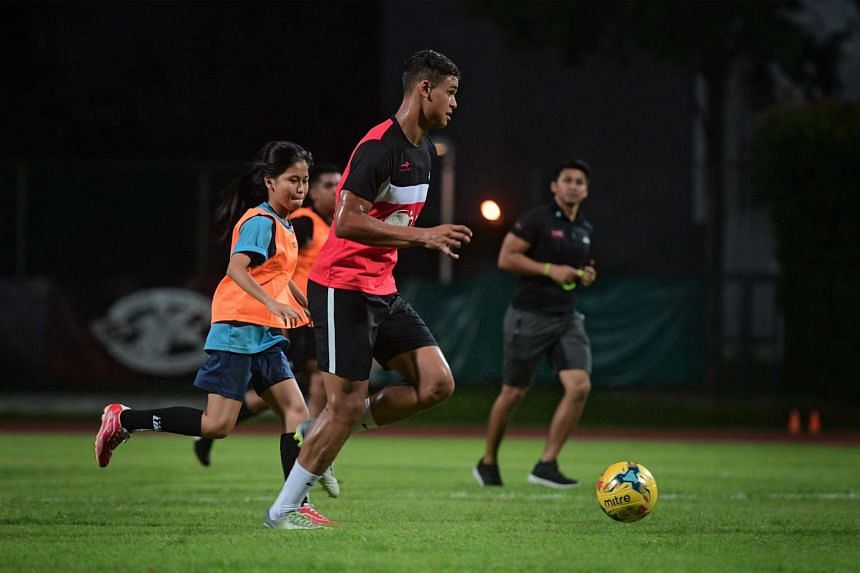 Irfan Fandi (centre) in action during a friendly soccer match with Saturday Night Light (SNL) youth participants and Delta League Youth at Bishan Stadium on March 11, 2017.