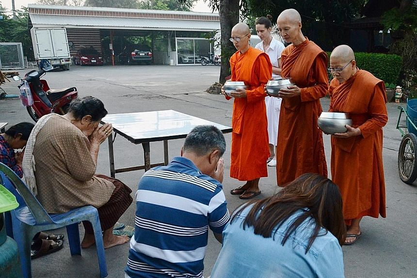 (Left) Female monks from Songdhammakalyani monastery blessing devotees after receiving alms. Dhammananda Bhikkuni (above), the abbess of the monastery, adjusting the position of one of her disciples during meditation practice. Female monk Ayya Visudd