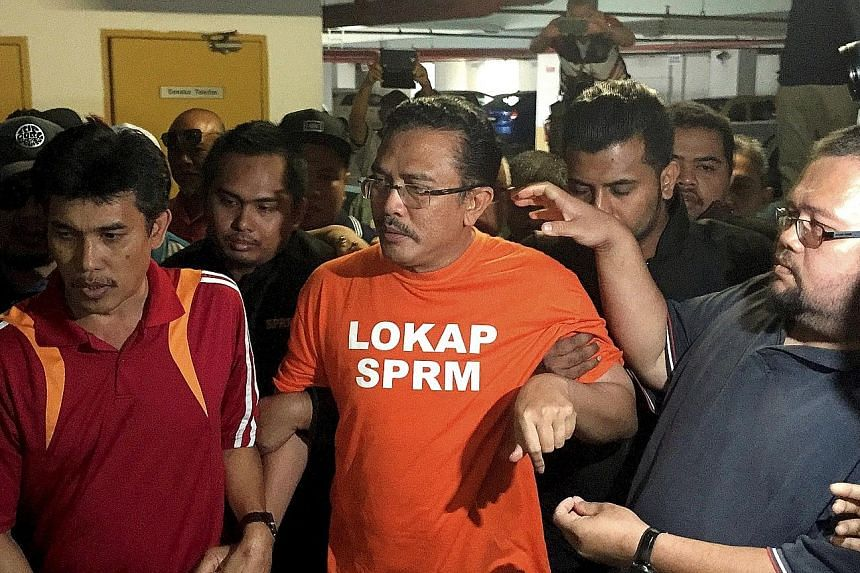 Mr Abdul Latif, clad in orange MACC lock-up attire, outside a courtroom yesterday. He is being held for seven days over a land scandal where kickbacks were allegedly received for converting land use.