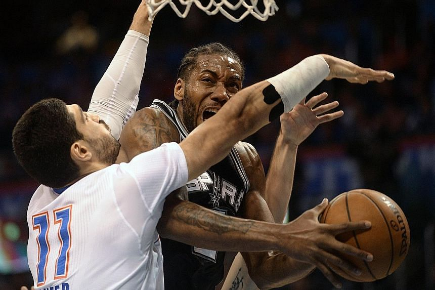 Spurs forward Kawhi Leonard (right) drives to the basket as Thunder centre Enes Kanter defends. Leonard scored a team-high 19 points.