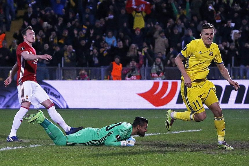 FC Rostov's Aleksandr Bukharov (right) celebrates levelling the score as Man United's Phil Jones and goalkeeper Sergio Romero react to losing their lead. The tie is finely poised at 1-1.