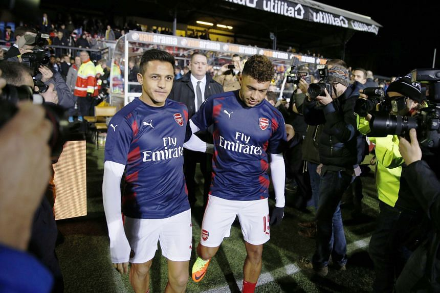 Arsenal's Alexis Sanchez (left) and Alex Oxlade-Chamberlain reportedly want to leave the club and their manager Arsene Wenger has to decide whether to start them against Lincoln.