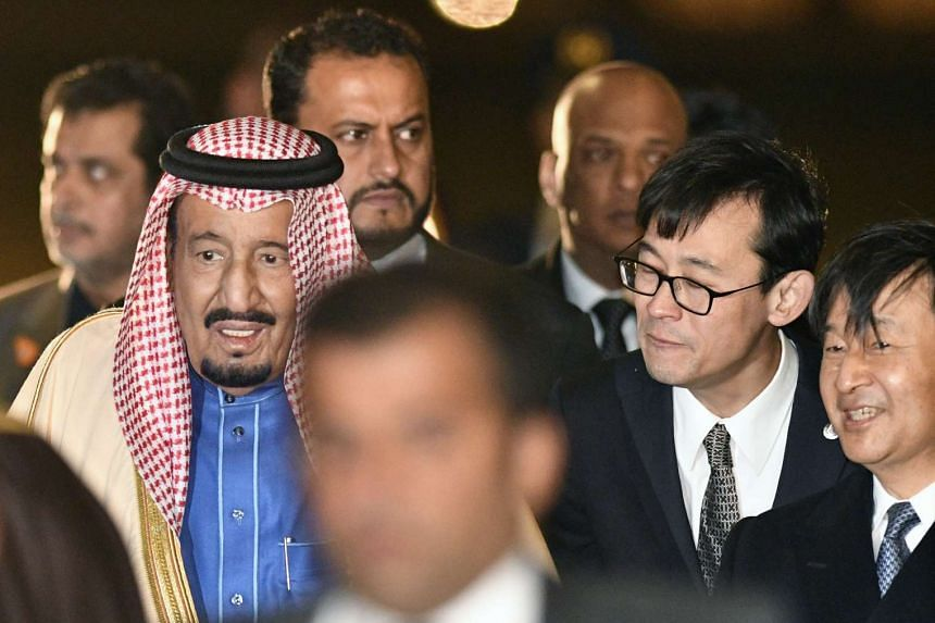 Saudi King Salman (left) being greeted by Japan's Crown Prince Naruhito (right) at Haneda Airport on March 12, 2017.
