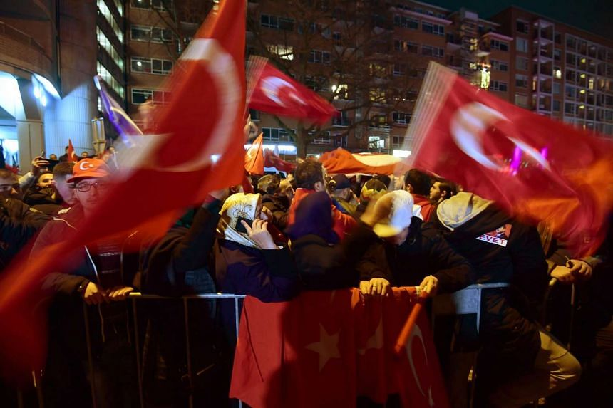 Turkish residents in the Netherlands waving Turkish flags during a gathering outside Turkey's consulate in Rotterdam on March 11, 2017.