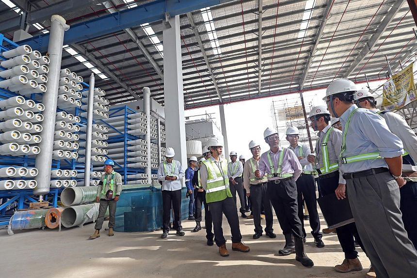 Minister for the Environment and Water Resources Masagos Zulkifli (in light pink shirt and high-cut boots) at the Tuas Desalination Plant 3 last month. In Parliament recently, Mr Masagos stressed the importance of pricing of water on sound economic princi