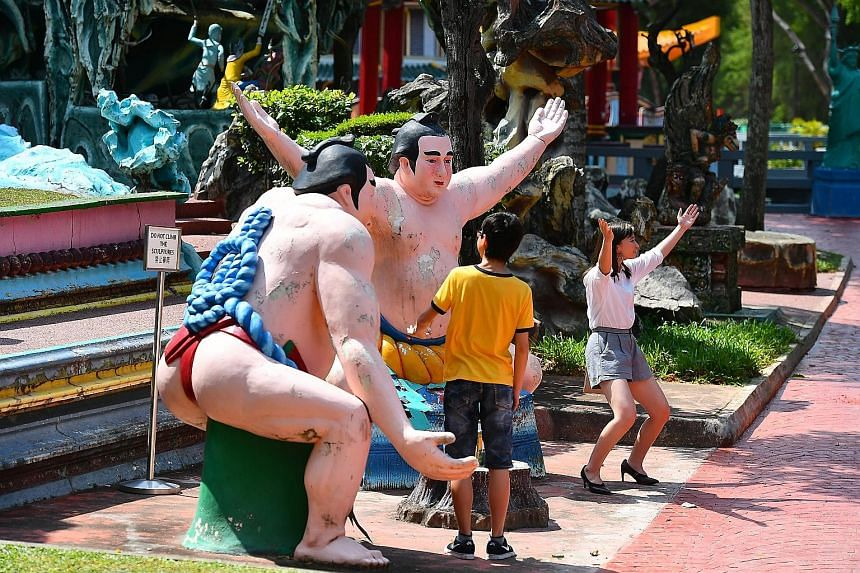 Visitors posing for photographs with statues at Haw Par Villa last Friday. Construction to upgrade its infrastructure and facilities is under way at the 80-year-old park, in a bid to improve visitorship.