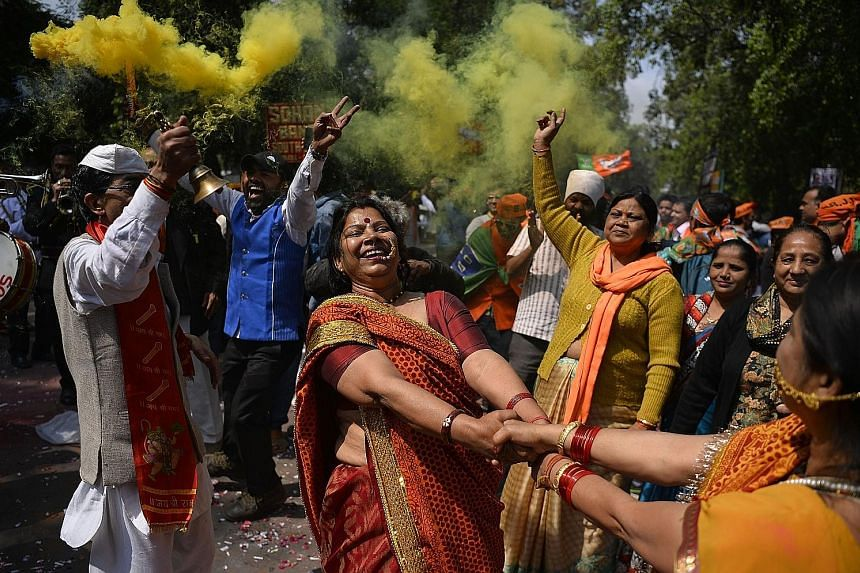 Supporters of India's Bharatiya Janata Party celebrating outside the party headquarters in New Delhi yesterday, after its landslide victory in Uttar Pradesh. The party was on course to win 309 of the 403 seats at stake in the state assembly, the bigg