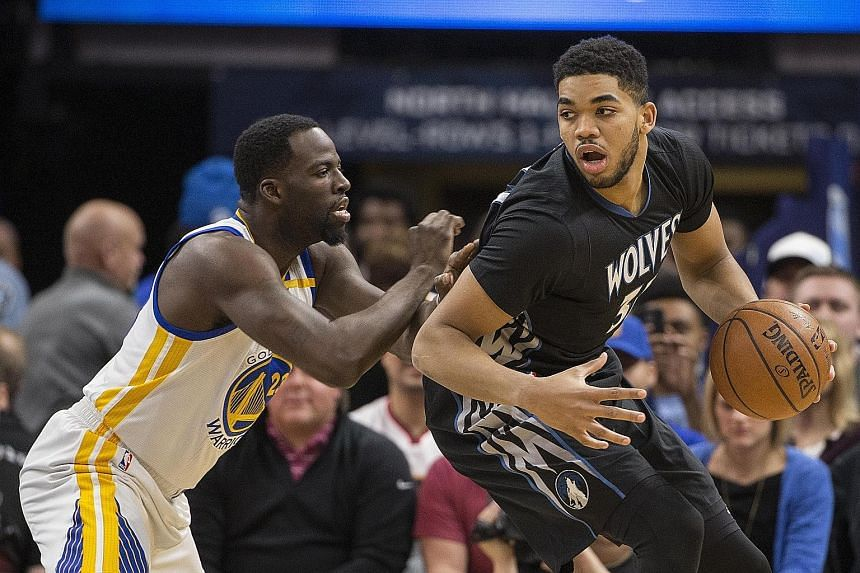 Timberwolves centre Karl-Anthony Towns protecting the ball from Warriors star Draymond Green in the NBA on Friday. Minnesota won 103-102.